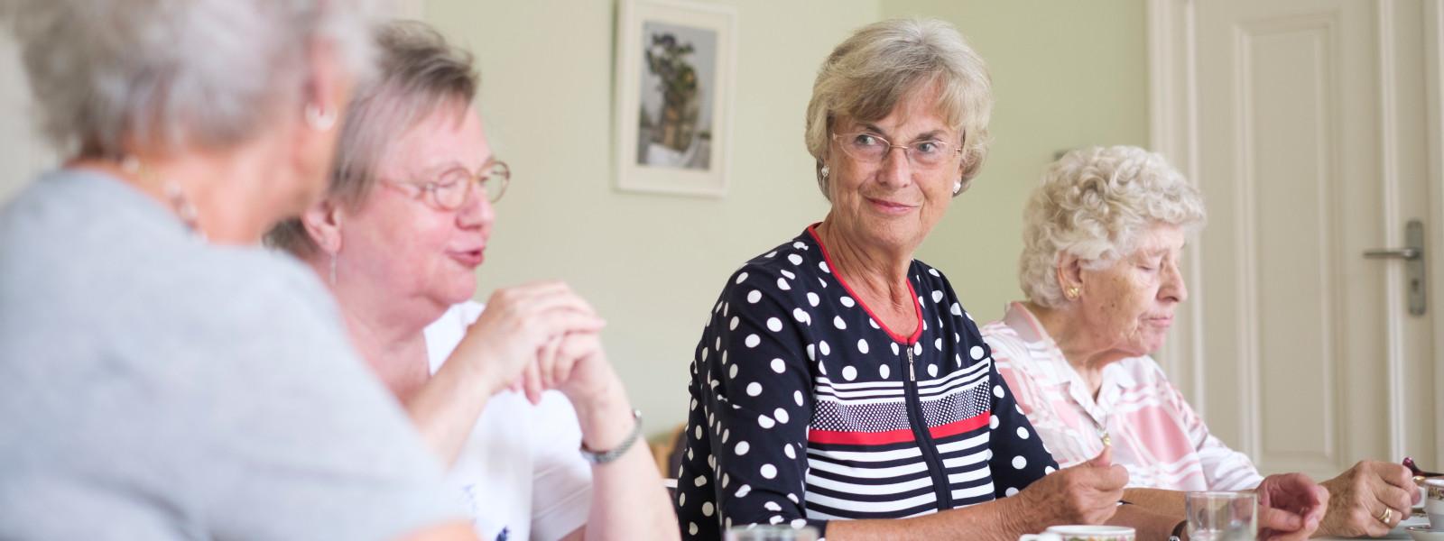Mehrere Seniorinnen sitzen an einem Tisch