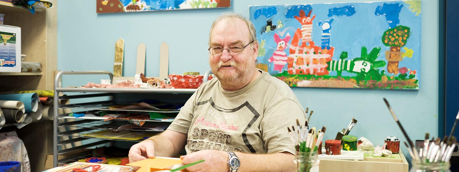 Ein Mann sitzt an einem Tisch und bastelt