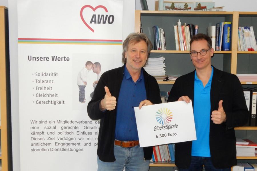 """Reinhard Zedler und Christoph Götz-Lee zeigen ein Schild mit der Aufschrift """"Glücksspirale"""""""